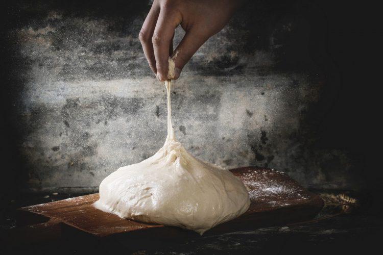 man baking pizza dough